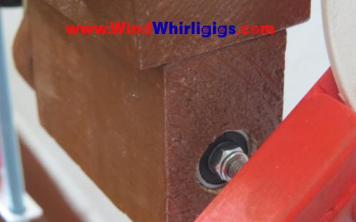 Part of wooden whirligig. The main drive shaft passes through the bearing.