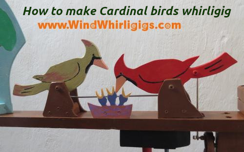 Cardinal bird whirligig. A pair of cardinal birds feed the chicks in the nest.