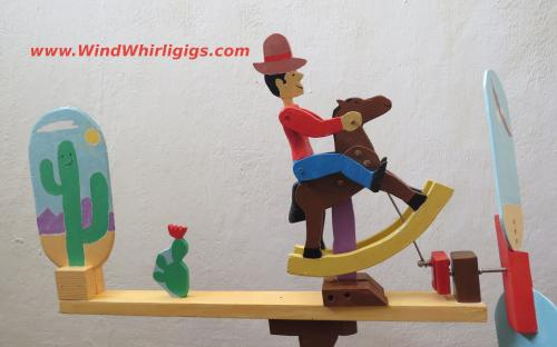 Whirligig. Cowboy riding a toy horse in a desert.