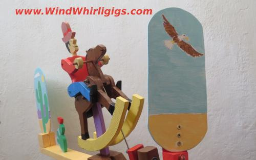 Whirligig. Cowboy riding a toy horse in a desert. Wind-driven wooden whirligig.