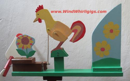 Rooster Whirligig. Cockerel pecks a sunflower. Wind-driven whirligig.